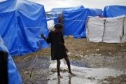 A girl crosses a puddle of water after heavy rains at a makeshift tent camp in Cite Soleil in Port-au-Prince in this file photo taken on February 26, 2010.
