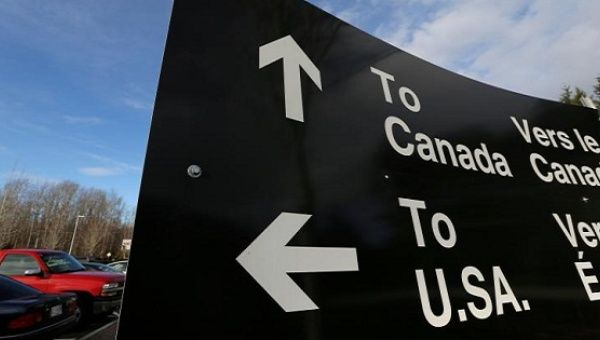A sign giving directions is seen in the parking lot of the United States-Canada border in Surrey, British Columbia, Canada, Feb. 16, 2017.
