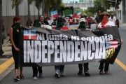 Puerto Ricans march in support of becoming an independent nation. The sign reads 'Neither (Financial Oversight and Management) Board, Nor Colony, Independence Now!'
