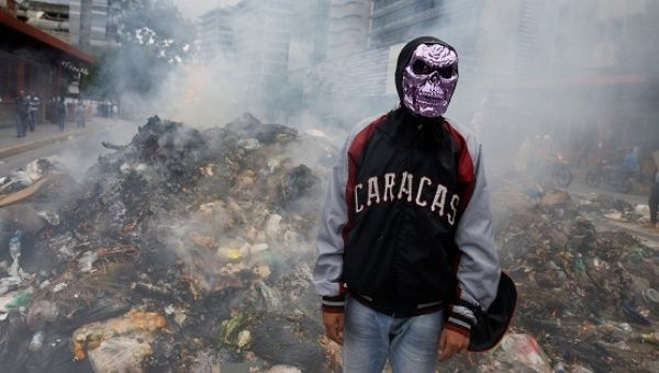A masked opposition protester stands in front of a burning pile of garbage built to block the street.