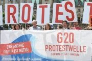 Protesters hold a banner in front of the townhall during a demonstration against the upcoming G20 summit in Hamburg.