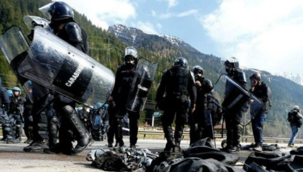Italian riot police wait for demonstrators during a protest against a plan to restrict access through the Brenner Pass between Italy and Austria, in Brenner .