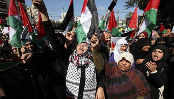 Palestinian women attend a rally calling for an end to Palestinian divisions to mark International Women
