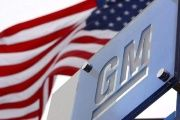 A GM logo stands next to a flag of the United States.