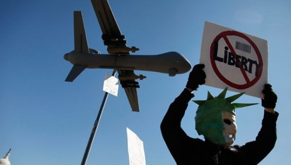 A protester wears a mask depicting a skull beneath the head of the Statue of Liberty, beneath a model of a US drone aircraft.