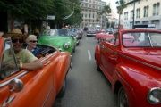 Tourists enjoy a ride in vintage cars in Old Havana.