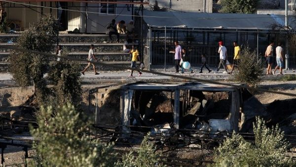 Migrants walk next to debris of burned shelters at the Moria refugee camp on the island of Lesbos, Greece, on July 10, 2017.
