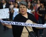 A Mexican protester against feminicide holds a sign: