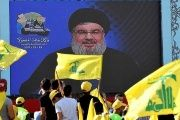 Nasrallah appears on a screen during a broadcast to speak to his supporters at an event marking Resistance and Liberation Day, May 25, 2017.