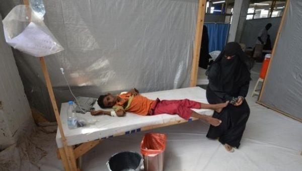 A woman sits next to a child infected with cholera in Yemen.