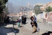 People run in panic after a Coalition airstrike hit Islamic State group fighters positions in the Tahrir neighborhood of Mosul, Iraq, on November 17, 2016.