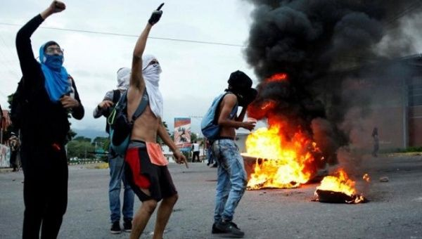 Opposition supporters shout as they burn tires during a protest.