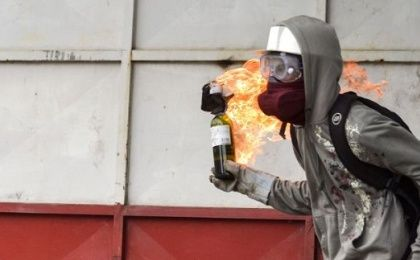 A Venezuelan right-wing opposition protester prepares to hurl a molotov cocktail.