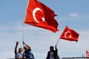 People wave Turkey's national flags as they arrive to attend a ceremony at the Bosphorus Bridge in Istanbul, Turkey, on July 15, 2017.