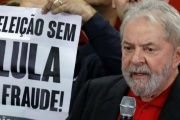 Lula speaks beside a placard that reads,