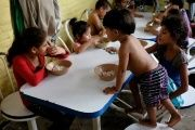 Children from Honduras, traveling with relatives to the U.S., have their meals at the Todo por ellos (All for them) immigrant shelter in Tapachula, Mexico.