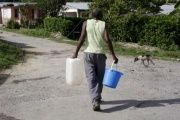 A man carries buckets of water while is searching a some of water at La Chusmita neighborhood in Consolacion del Sur, Pinar del Rio province, Cuba.