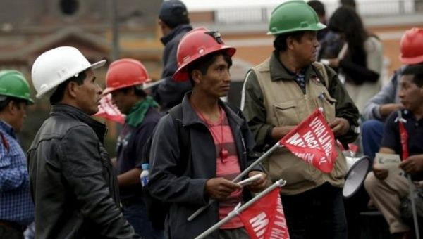 Miners hold signs during a national strike in Lima, Peru, May 21, 2015.
