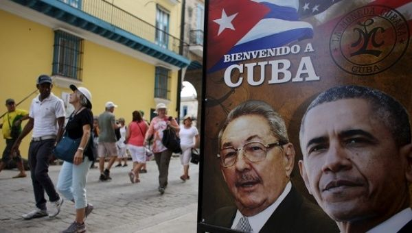 Tourists walk past images of Cuban President Raul Castro and his former U.S. counterpart Barack Obama in Havana, March 17, 2016.