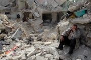 A Syrian man sits by homes destroyed by airstrikes and combat.