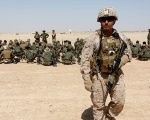 A U.S. Marine walks near Afghan National Army (ANA) soldiers during training in Helmand province, Afghanistan, on July 5, 2017.