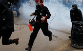 Demonstrators run from a stun grenade while protesting against U.S. President Donald Trump