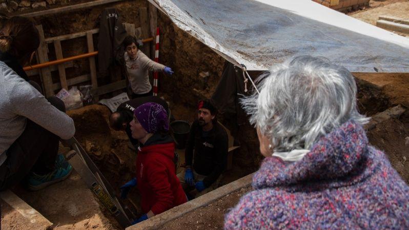 Ascensión Mendieta mira el trabajo que hacen los arqueólogos y voluntarios en la fosa.