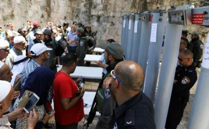 Palestinians stand in front of Israeli forces and newly-installed metal detectors at an entrance to the al-Aqsa Mosque  in the Old City of occupied East Jerusalem.