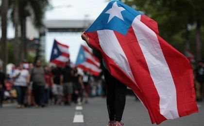 Protester wrapped in Puerto Rican flag.