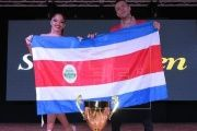 The winning couple pose with their country's flag after winning the title, July 26, 2017, San Juan, Puerto Rico.