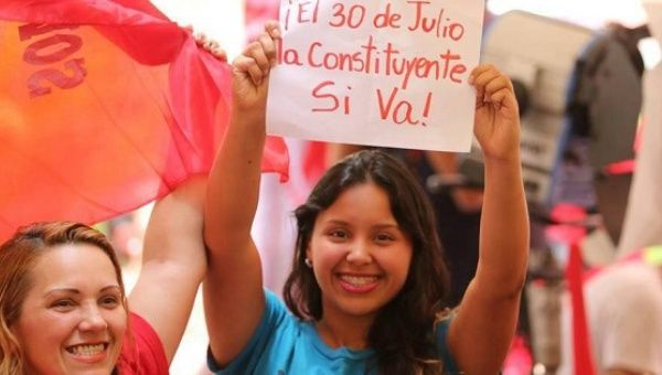 "A woman holds a sign that reads ""On July 30, the Constituent Assembly will happen"" during a rally in Caracas."