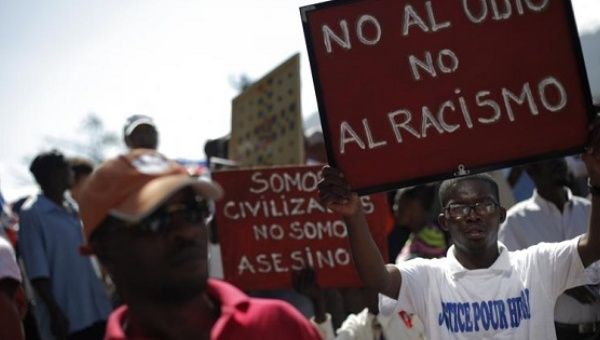 Haitians hold signs during a march against racism in Port-au-Prince, Haiti, in 2015