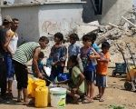 Palestinian children collect water in Khan Yunis, located in the southern Gaza Strip.