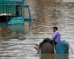 A man uses a makeshift raft to move out of a flooded neighborhood in Ahmedabad.