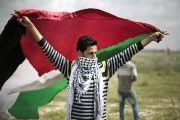 A protester waves a Palestinian flag towards the Israeli border fence during a protest at the border between Israel and the Gaza Strip.