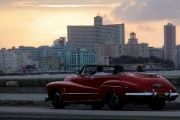 Sunsets over Havana's Malecon as tourists ride in a convertible car.