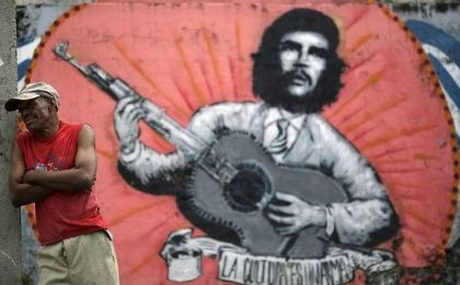 A man stands next to a mural of Ernesto