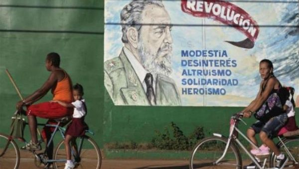 "Cubans bicycle pass an image of Fidel Castro which says: ""Revolution, modesty, disinterest, altruism, solidarity, and heroism."""