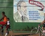 Cubans bicycle pass an image of Fidel Castro which says: