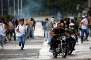 Demonstrators run and ride their motorcycles near Fuerte Paramacay military base, August 6.