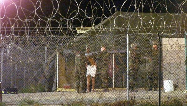 Marines at Camp X-Ray at the Naval Base at Guantanamo Bay, Cuba escort a newly arriving detainee into a processing tent.