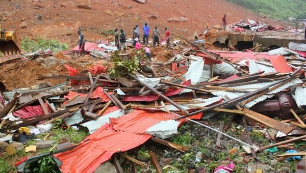People inspect the damage after a mudslide in the mountain town of Regent, Sierra Leone August 14, 2017.