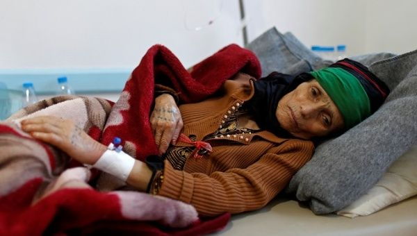 A woman with suspected cholera infection lies on a bed at a cholera treatment center in Sanaa.
