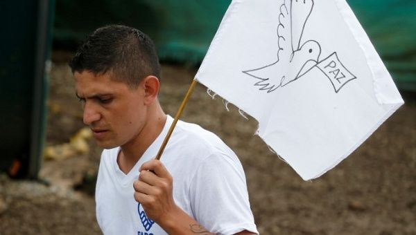 A FARC rebel waves a peace flag during the final act of abandonment of arms in Mesetas, Colombia, on June 27,2017.