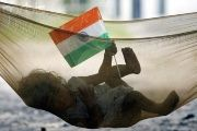 Indian child plays with Indian national flag while lying in hammock in a slum in Chandigarh, India.