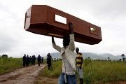 A man carries an empty coffin at the Paloko cemetery in Waterloo, Sierra Leone.