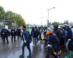 French police look on as migrants walk towards waiting buses as they are evacuated from a makeshift camp at Porte de la Chapelle, in the north of Paris, on August 18, 2017.