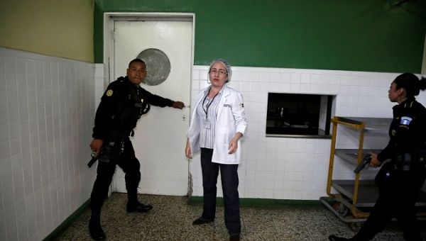 Police officers react after suspected gang members attacked a hospital in Guatemala City.
