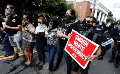 Counter-protesters lock arms as police try to disperse them, after members of the Ku Klux Klan rallied in support of Confederate monuments in Charlottesville, Virginia