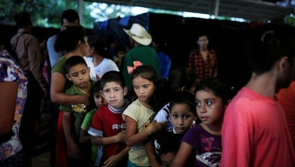 Children queue at dinner time at a shelter for displaced people from El Castano village in the town of Caluco, El Salvador.